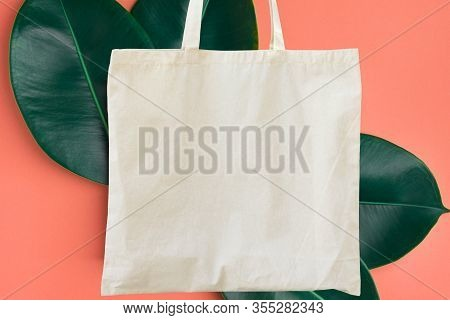 Blank Cotton Shite Shopper Tote Bag On Pink Background With Green Leaves. Mock Up Template For Produ