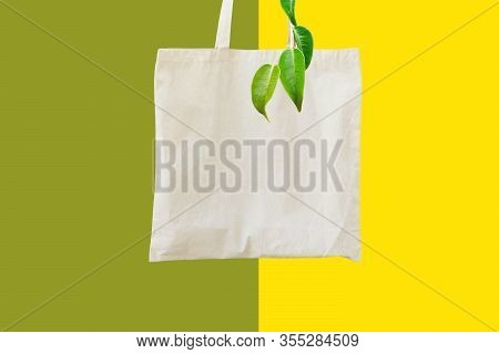 Blank Cotton Shite Shopper Tote Bag On Duotone Yellow Green Background Dangling Tree Branch. Mock Up
