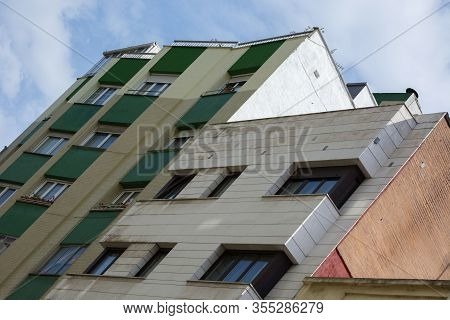 Photo Of A Several Colours Building With Several Windows, Cloudy Sky And Sunlight.