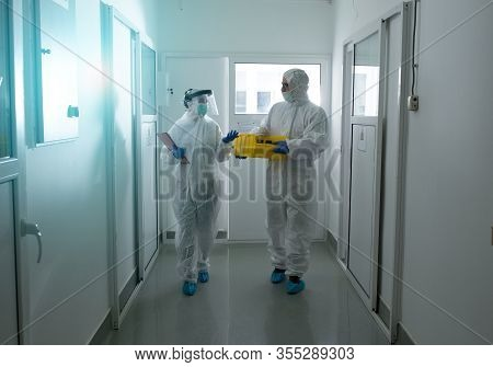 Two Biologists In Protective Suits Carrying Samples In Laboratory Hallway