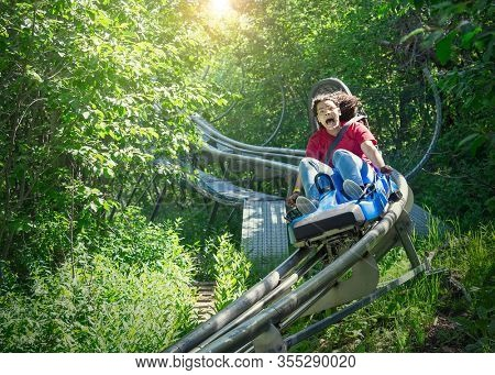 Screaming teen girl riding downhill on an outdoor roller coaster on a warm summer day. She has a fun expression on her face as she enjoys a thrilling ride on an amusement park ride
