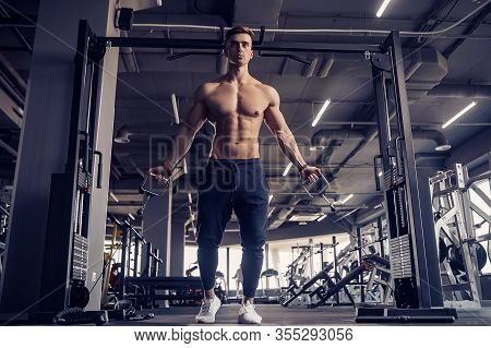 Muscular Fitness Bodybuilder Doing Heavy Weight Exercise For Pectoral Muscles On Machine With Cable