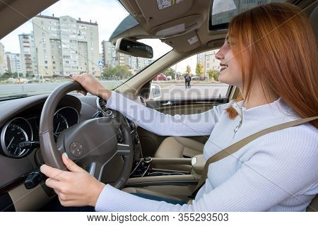 Wide Angle View Of Young Redhead Woman Driver Fastened By Seatbelt Driving A Car Smiling Happily.