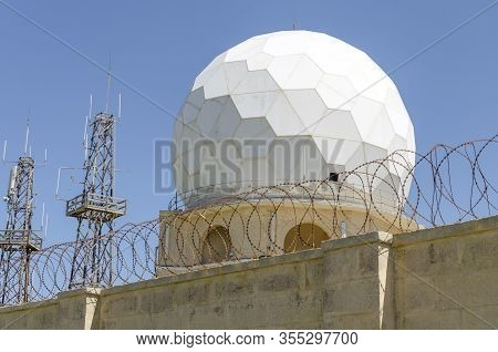 Aircraft Radar Dome Behind Arb Wire And Stone Wall With Blue Sky In The Background