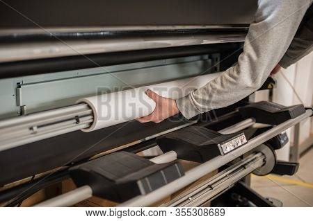 Technician Operator Changes Paper Roll On Large Printer Plotter Machine