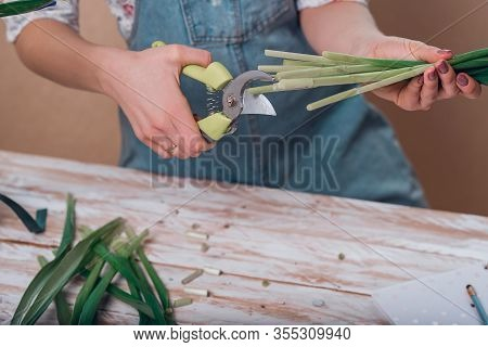 Hands Of Young Woman Florist Cutting Fresh Flowers Making Bouquet Of Fleur-de-lises On Table.
