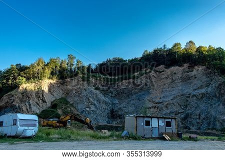 Forest On Top Of A Mountain Quarry With Bulldozer, Shack And Camper Van In The Foreground