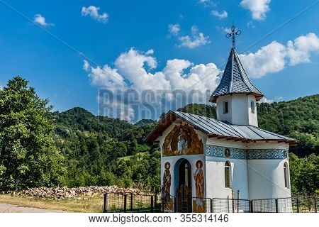 Small Church On The Side Of The Road With Wooden Logs Puffy Clouds And Forest In The Background