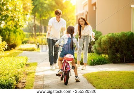 Daughter Train To Ride A Bicycle From Her Moter And Her Father, This Image Can Use For Family, Outdo