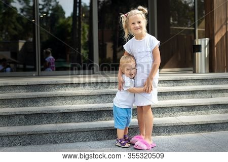 Two Cute Adorable Caucasian Blond Little Siblings Standing And Hugging On Entrance Residential Build
