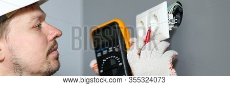 Electrician In Helmet Measures Level Electricity. Combined Electrical Measuring Instrument, Combinin