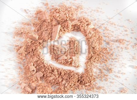 Scattered Crumbs Of Face Powder Or Eye Shadow In The Shape Of A Heart On A White Background, Makeup