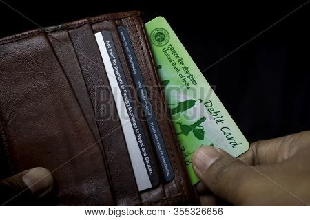 United Bank Of India Ubi Atm Debit Card In Brown Wallet Held In Hand On Black Background
