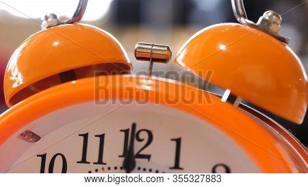 Close Up Of Retro Alarm Clock Going Off On Blurred Background. Stock Fooatge. Orange Alarm Clock Det