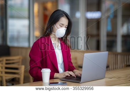 Asian Girl Use A Protection Mask For Prevent Pm 2.5 And Corona Viruus Or Covic 19 In Office In Bangk