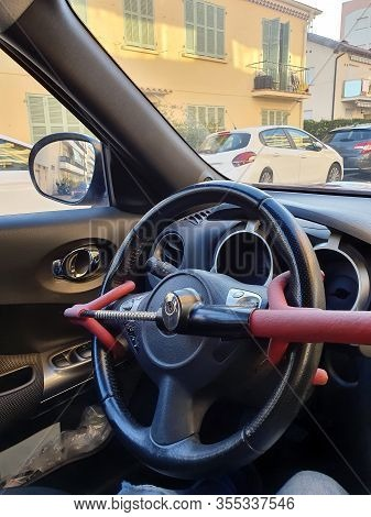 Close Up View Of Anti-theft Car Steering Wheel Lock Car Security. Black And Red Colors