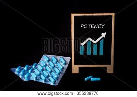 Two Packs Of Blue Capsules And The Word Potency On A Chalkboard. Pills For Mens Health And Sexual En