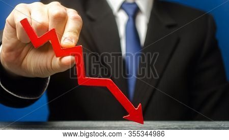 Businessman Holds A Red Down Arrow. The Concept Of Reducing Profits And Income. Recession And The Fi