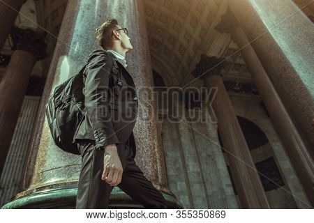 A portrait of a goodlooking young student walking in the street. Men's formal fashion, success, education.
