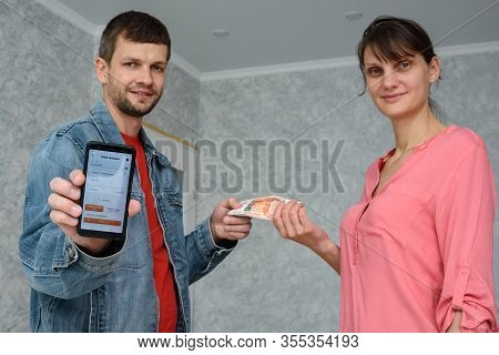 Anapa, Russia - March 11, 2020: A Self-employed Man Receives Money From A Girl For Repairing A Room