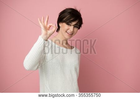 Female portrait with positive expressions and ok gesture. Beautiful young woman happy and excited expressing winning gesture. Successful and celebrating victory, triumphant, studio shot over pink