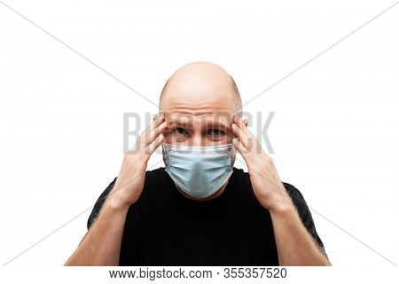 Human population virus, infection, flu disease prevention and industrial exhaust emissions protection concept - young adult bald head man wearing respiratory protective medical mask suffers headache