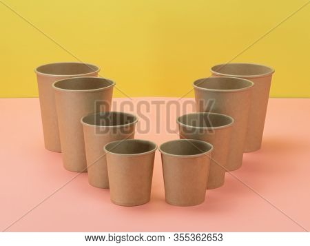 Eco-friendly Paper Cups In Pink And Yellow Background. Bio Ware.