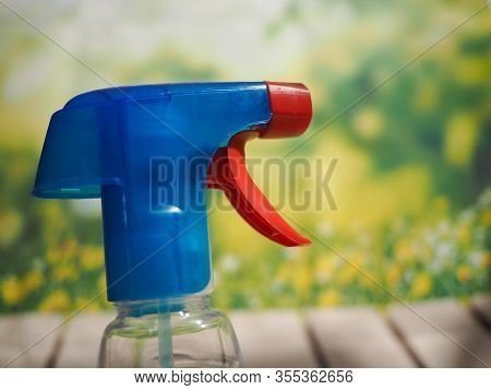 Water Or Detergent Spray Bottle Against Wooden Table And Green Natural Background