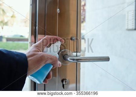 closeup of a caucasian man disinfecting the handle of the front door of an apartment building by spraying a blue sanitizer from a bottle