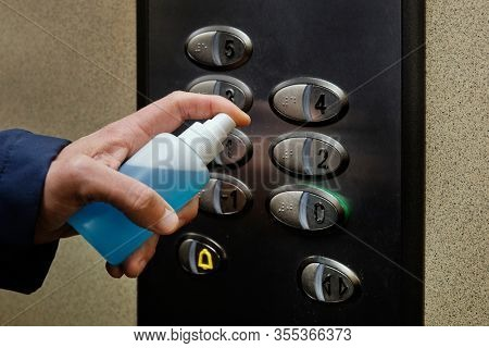 closeup of a caucasian man disinfecting the buttons of an elevator, in an apartment building or office building, by spraying a blue sanitizer from a bottle
