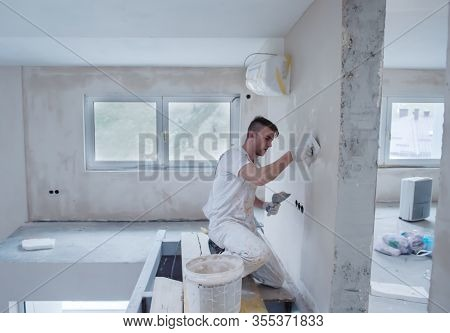 young professional construction worker plastering on gypsum walls inside the new big modern two levels apartment