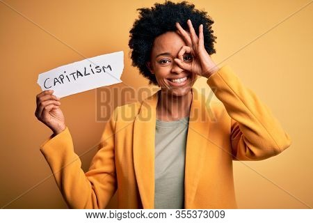 African American afro businesswoman with curly hair holding paper with capitalism message with happy face smiling doing ok sign with hand on eye looking through fingers
