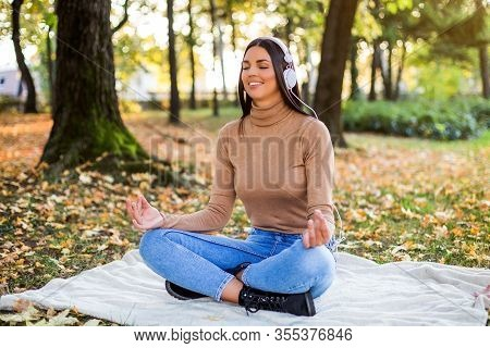Beautiful Woman Meditating And Listening Music While Resting And Enjoys In Autumn In The Park.