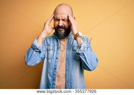 Handsome bald man with beard wearing casual denim jacket and striped t-shirt with hand on head for pain in head because stress. Suffering migraine.