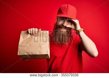 Redhead Irish delivery man with beard holding takeaway paper bag over red background stressed with hand on head, shocked with shame and surprise face, angry and frustrated. Fear and upset for mistake.