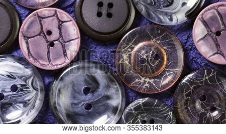 Abstract Background.on A Purple Textured Background, A Group Of Buttons For Clothes.round Buttons Fo