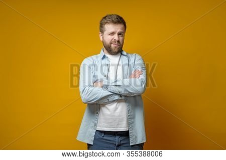 Man With A Strange Expression On Face Is Standing With Arms Crossed, He Covered One Eye And The Othe