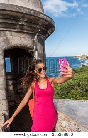 Puerto RIco San Juan city travel tourist Asian woman taking selfie at popular tourists attraction, tower of Castillo San Felipe del Morro.