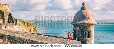 San Juan Puerto Rico travel happy tourist woman waving open arms in happiness at watch tower of Castillo San Felipe del Morro panoramic banner background.