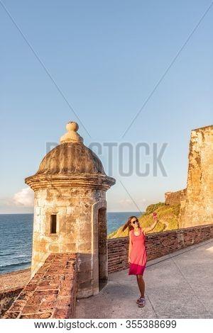 San Juan Puerto Rico tourists visiting famous landmark of Old Town, woman tourist taking selfie at Castillo San Felipe del Morro.