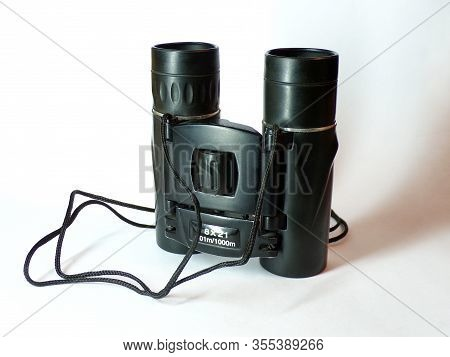 Binoculars. Binoculars On A White Background With A Shadow. Binoculars Made Of Black Metal Close-up.