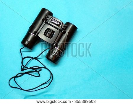 Binoculars. Background Binoculars Top View Of Copyspace. Binoculars With A Rope Close- Up On A Blue
