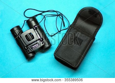 Binoculars. Binoculars With A Case Top View On A Blue Background Close-up. Binoculars For Hunting An