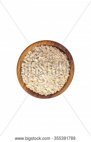 Raw Oat-flakes In Wooden Bowl. Isolated On White Background. Top View On Uncooked Dry Rolled Oatmeal