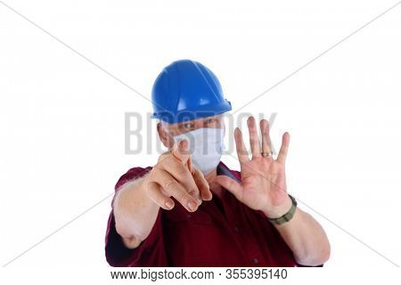 2019 Novel Coronavirus. 2019-nCoV. Wuhan, China 2019 Novel Coronavirus. Construction Worker holds out his hand in a Warning Sign against COVID19.  World Wide Pandemic. World Wide Coronavirus Pandemic.