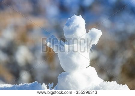 Close Up Of A Miniature Snowman In Front Of A Blurry Wintery Background.