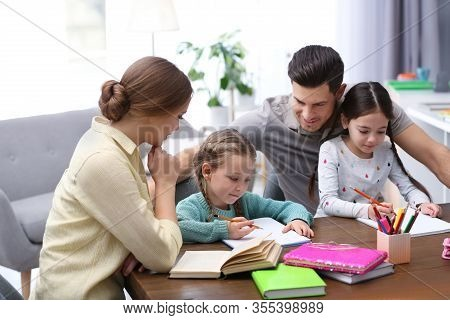 Parents Helping Their Daughters With Homework At Table Indoors