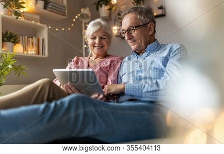 Mature couple using a laptop while relaxing at home