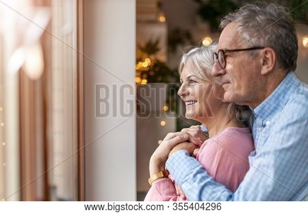 Mature couple looking out through window at home