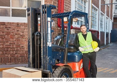 Satisfied forklift driver with his forklift before the freight forwarder